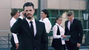 Retrato del hombre de negocios serio pero contento que hace una llamada de teléfono y a cuatro compañeros de trabajo del negocio  metrajes