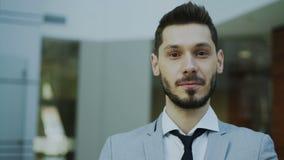 Retrato del hombre de negocios sonriente joven acertado que mira en cámara en oficina moderna