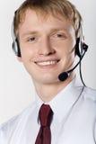 Retrato del hombre de negocios sonriente joven con el receptor de cabeza en blanco Fotografía de archivo libre de regalías