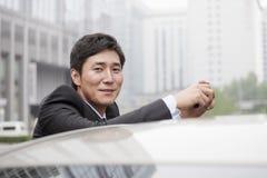 Retrato del hombre de negocios sonriente Leaning On Car Imagen de archivo