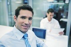 Retrato del hombre de negocios sonriente que trabaja en oficina, mirando el camer imagen de archivo