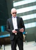 Retrato del hombre de negocios sonriente que usa la tableta del ordenador Foto de archivo libre de regalías