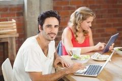Retrato del hombre de negocios usando el ordenador portátil con el colega en fondo en la oficina Foto de archivo libre de regalías