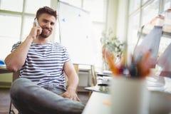 Retrato del hombre de negocios usando el teléfono móvil mientras que se sienta en oficina Fotos de archivo