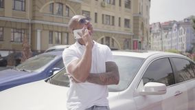 Retrato del hombre de Oriente Medio calvo confiado acertado hermoso que habla por el teléfono celular que coloca después su coche metrajes
