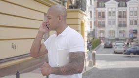 Retrato del hombre de Oriente Medio calvo confiado acertado hermoso que habla por la situación del teléfono celular en la calle a almacen de video
