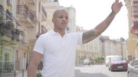 Retrato del hombre de Oriente Medio calvo confiado hermoso que aumenta su mano para coger un taxi en la calle de la ciudad vieja almacen de video