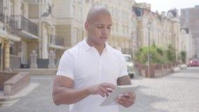 Retrato del hombre de Oriente Medio calvo confiado hermoso que mecanografía en la situación de la tableta en la calle delante de  almacen de video