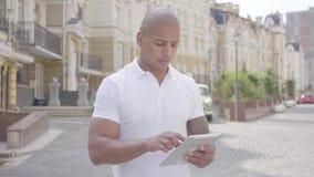Retrato del hombre de Oriente Medio calvo confiado hermoso que mecanografía en la situación de la tableta en la calle delante de  metrajes