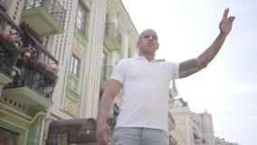Retrato del hombre de Oriente Medio calvo confiado que aumenta su mano para coger un taxi en la calle de la ciudad vieja Ocio de metrajes