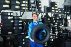 Retrato del hombre del mecánico con los neumáticos autos en taller Imágenes de archivo libres de regalías