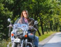 Retrato del hombre del motorista con la barba que se sienta en su motocicleta Imagen de archivo libre de regalías