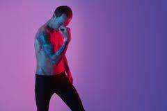 Retrato del hombre deportivo de la aptitud que muestra el tríceps muscular, manos tatuadas, inconformista Luz de destello del est Foto de archivo libre de regalías