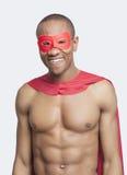 Retrato del hombre descamisado joven en traje del super héroe que sonríe contra fondo gris Imágenes de archivo libres de regalías