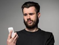 Retrato del hombre desconcertado que habla en el teléfono Foto de archivo