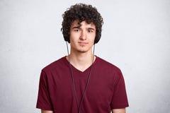 Retrato del hombre dirigido rizado, camiseta marrón casual que lleva, presentando en estudio mientras que escucha la música en lo imagenes de archivo