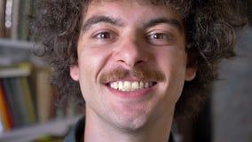 Retrato del hombre divertido loco que se coloca en biblioteca y que se ríe de la cámara, estantes en fondo metrajes