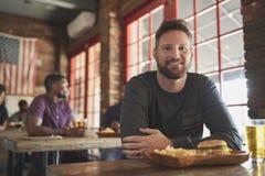 Retrato del hombre en barra de deportes que come la hamburguesa y las fritadas foto de archivo