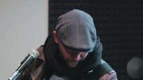 Retrato del hombre en el casquillo y la bufanda que mueven su cabeza y que tocan la guitarra almacen de video
