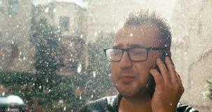 Retrato del hombre enojado con las lentes que grita en alguien mientras que habla en el teléfono móvil en lluvia cantidad 4k metrajes