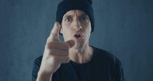 Retrato del hombre enojado en casquillo negro que grita con la agresión Amenaza de la violencia almacen de video