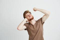 Retrato del hombre enojado joven con los oídos cerrados de la barba que miran para arriba que muestran el puño sobre el fondo bla Foto de archivo libre de regalías