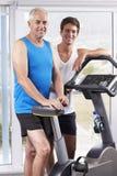 Retrato del hombre envejecido centro con el instructor personal In Gym imagen de archivo