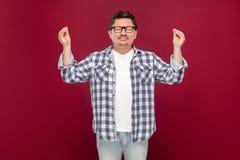 Retrato del hombre envejecido medio hermoso en camisa a cuadros casual y las lentes que se colocan con los brazos aumentados en a foto de archivo