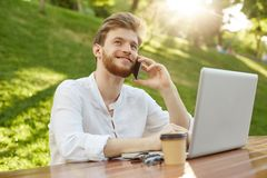Retrato del hombre europeo acertado joven del jengibre con el peinado elegante y de la barba en la camisa blanca que se sienta en Imagenes de archivo