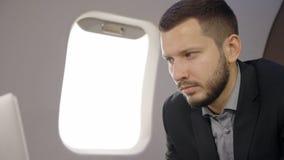 Retrato del hombre experto del analista del inversor que trabaja en el ordenador portátil en el avión metrajes