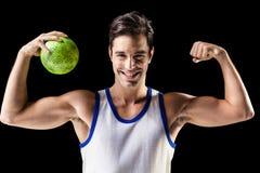 Retrato del hombre feliz del atleta que sostiene la bola y que muestra los músculos Imagen de archivo libre de regalías