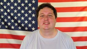 Retrato del hombre feliz en el fondo de una bandera de los E.E.U.U. almacen de video