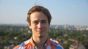 Retrato del hombre feliz joven que se sienta en el tejado del edificio alto con el fondo borroso del paisaje urbano Individuo her almacen de metraje de vídeo