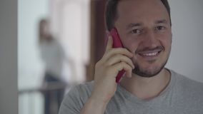 Retrato del hombre feliz que habla con su paramour por el teléfono móvil mientras que aparece su esposa detrás y el oír por casua metrajes