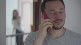 Retrato del hombre feliz que habla con su paramour por el teléfono móvil mientras que aparece su esposa detrás y el oír por casua almacen de metraje de vídeo