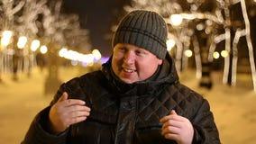 Retrato del hombre feliz que invita al aire libre durante la tarde fría del invierno almacen de metraje de vídeo