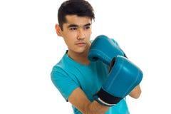 Retrato del hombre fuerte joven en el encajonamiento practicante de la camisa azul en los guantes aislados en el fondo blanco Fotos de archivo