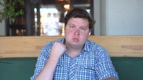 Retrato del hombre gordo enojado que sacude su puño en café o restaurante metrajes