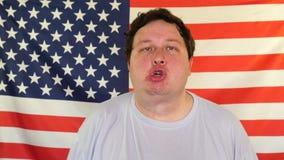 Retrato del hombre gordo que hace caras divertidas en el fondo de una bandera de los E.E.U.U. metrajes