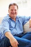 Retrato del hombre gordo que se sienta en el sofá Foto de archivo