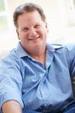 Retrato del hombre gordo que se sienta en el sofá Imagenes de archivo