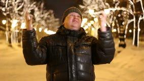 Retrato del hombre grande joven satisfecho que celebra con aire libre aumentado del brazo durante noche fría del invierno metrajes