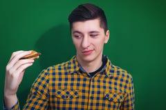 Retrato del hombre hambriento que mira la hamburguesa grande Foto de archivo