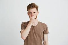 Retrato del hombre hermoso brutal joven con la barba que frunce el ceño mirando la cámara que lleva a cabo la mano en boca sobre  Fotografía de archivo libre de regalías