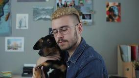 Retrato del hombre hermoso caucásico con los vidrios y el pelo amarillo del corte de pelo elegante que sientan en casa vuelta del metrajes