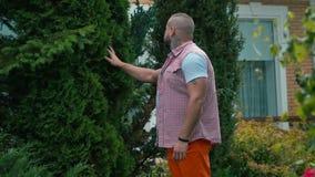 Retrato del hombre hermoso cerca del árboles verdes en el patio metrajes