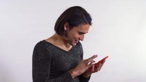 Retrato del hombre hermoso con el maquillaje que manda un SMS en su sonrisa anaranjada linda del teléfono celular Hombre del tran almacen de video