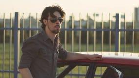 Retrato del hombre hermoso con su coche potente clásico viejo en la calle, en la puesta del sol o la salida del sol almacen de video
