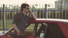 Retrato del hombre hermoso con su coche potente clásico viejo en la calle, en la puesta del sol o la salida del sol metrajes