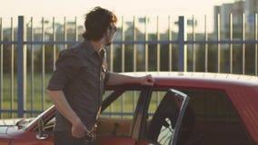 Retrato del hombre hermoso con su coche potente clásico viejo en la calle, en la puesta del sol o la salida del sol almacen de metraje de vídeo